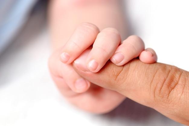 Mała rączka syna trzymająca palec ojca
