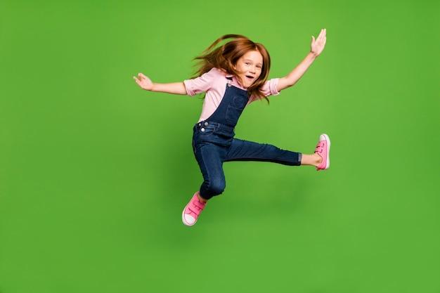 Mała ruda dziewczyna pozuje na zielonej ścianie