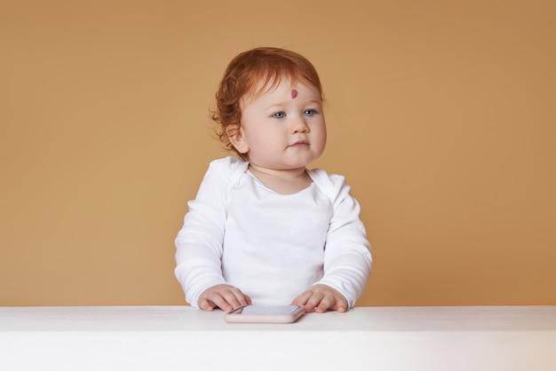 Mała rudowłosa dziewczynka bawi się na beżowym tle. wielki pieprzyk na czole, nie jak wszyscy inni