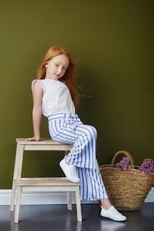 Mała rudowłosa dziewczynka z koszem kwiatów pozowanie na oliwkowym tle. wiosna portret rudej dziewczyny o niebieskich oczach. włosy w kolorze ognia, norweska nastolatka