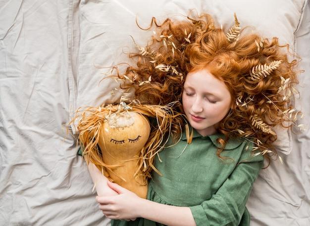 Mała rudowłosa wiedźma kładzie swoją dyniową dziewczynę do łóżka.