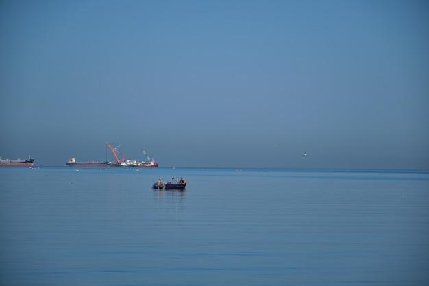 Mała rybak łódź na morzu. mała łódź rybacka unosząca się na morzu w pobliżu morza ze statkiem towarowym