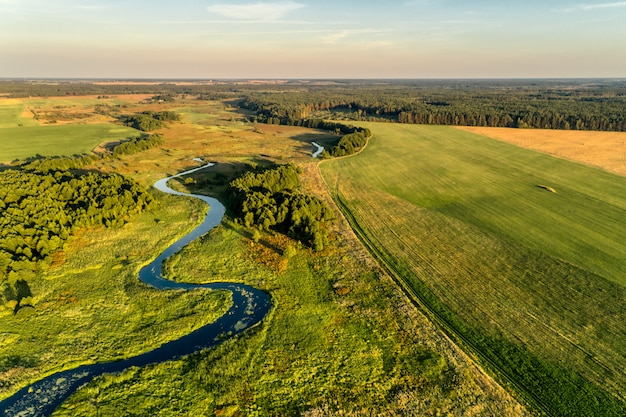 Mała rzeka przepływająca przez łąki i pola uprawne. widok z lotu ptaka. wieczorem strzał z zachodzącego słońca.