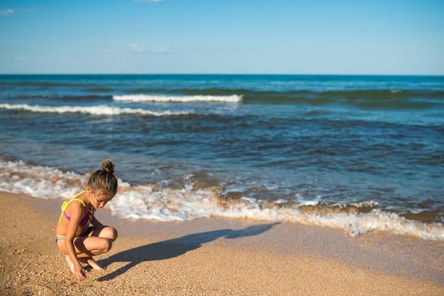 Mała samotna dziewczynka, siedząc na tle morza, pisze coś na piasku
