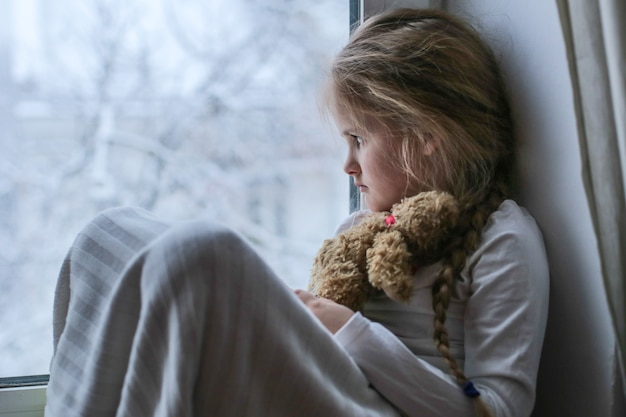 Mała samotna dziewczynka siedzi i smutno wygląda przez okno