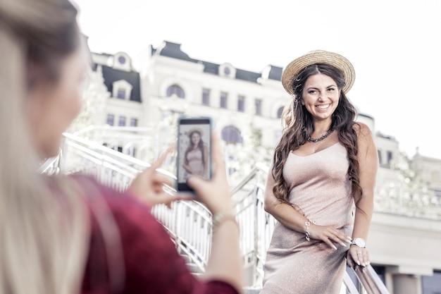 Mała sesja zdjęciowa. szczęśliwa radosna kobieta uśmiecha się podczas fotografowania przez swojego przyjaciela
