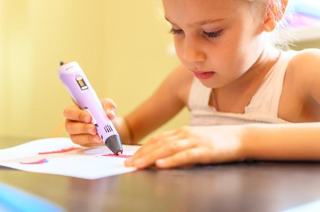 Mała siedmioletnia dziewczynka rysuje piórem 3d i plastikiem w domu. kreatywność i majsterkowanie dzieci