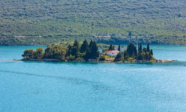 Mała skalista wyspa z drzewami i domem w pobliżu wybrzeża adriatyku (chorwacja)