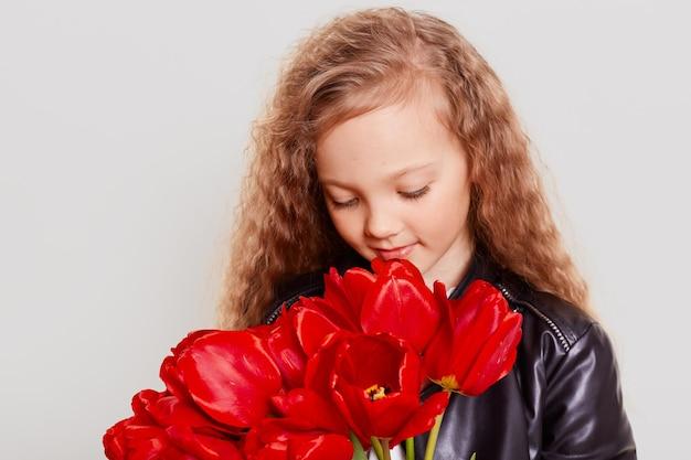 Mała śliczna blondynka trzyma w rękach bukiet czerwonych tulipanów, pachnie pięknymi kwiatami, patrzy w dół, ma marzycielski wygląd, ubiera skórzaną kurtkę