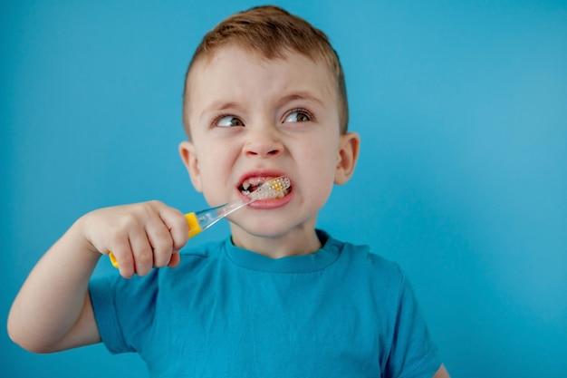Mała śliczna chłopiec szczotkuje jego zęby na błękit ścianie