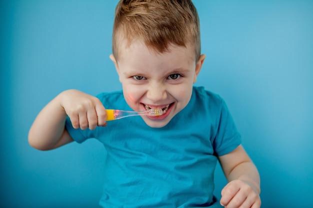 Mała śliczna chłopiec szczotkuje jego zęby na błękitnym tle