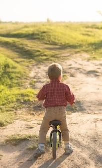 Mała śliczna dzieciak chłopiec na bicyklu na lata lub autmn dniu. zdrowe szczęśliwe dziecko zabawy z rowerem na rowerze.