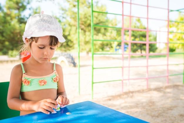 Mała śliczna dziewczyna bawi się lalkami na świeżym powietrzu, relaksując się na plaży w gorący letni dzień. koncepcja aktywnych gier dla dzieci.