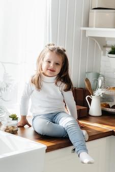 Mała śliczna dziewczyna bawić się w kuchni, szczęście, rodzina. gotowanie.