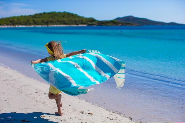 Mała śliczna dziewczyna bawić się z ręcznikiem plażowym