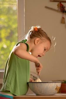 Mała śliczna dziewczyna gotuje w kuchni. ciesz się robieniem ciasteczek