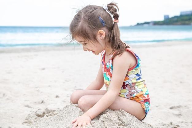 Mała śliczna dziewczyna gra w piasku na plaży nad morzem. letnia rozrywka i rekreacja.