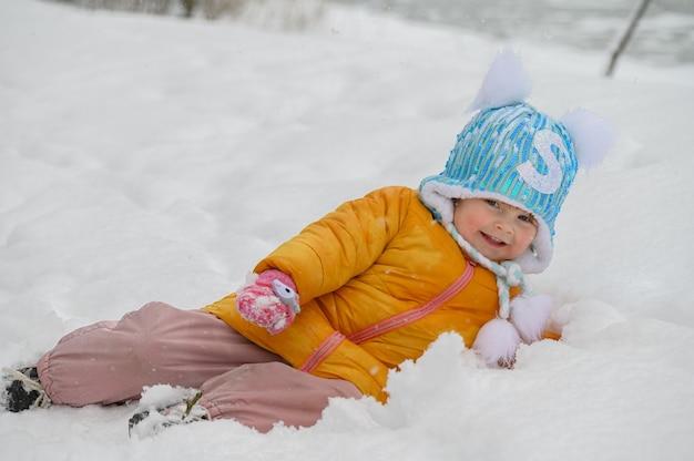 Mała śliczna dziewczyna gra w śniegu