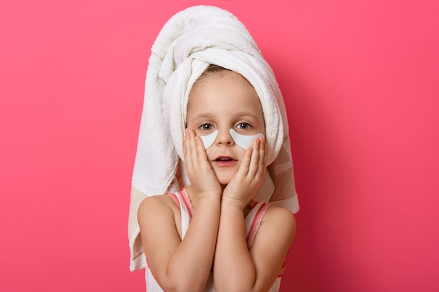 Mała śliczna dziewczyna jest ubranym białego ręcznika na głowie, pozuje z łatami pod oczami