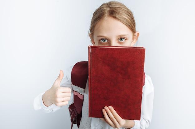 Mała śliczna dziewczyna jest uczennicą, wskazując na książkę, biała ściana