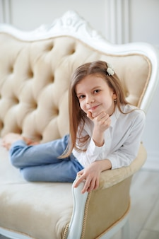 Mała śliczna dziewczyna kłama na kanapie w pokoju