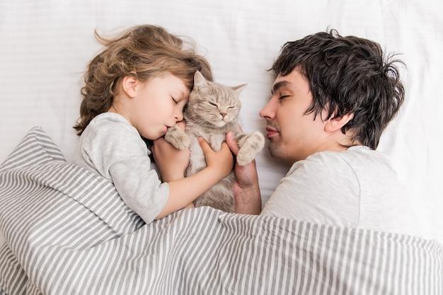 Mała śliczna dziewczyna leży i bawi się z tatą i kotem na kanapie.