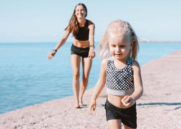 Mała śliczna dziewczyna patrzeje dostosowywać mamy na plaży