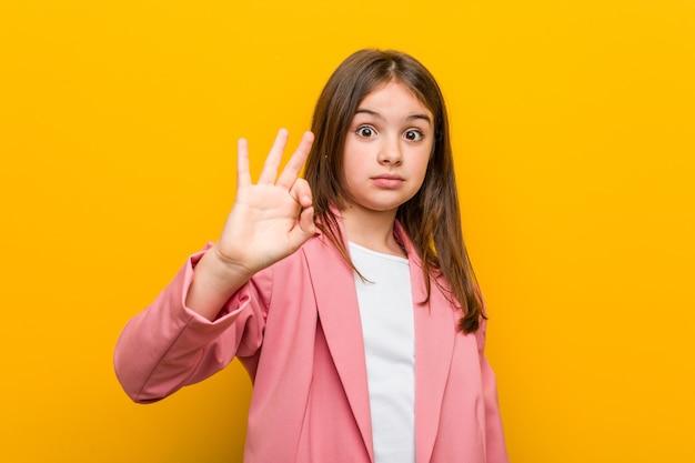 Mała śliczna dziewczyna pokazuje ok gest