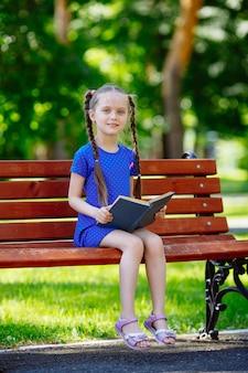 Mała śliczna dziewczyna siedzi na ławce i czyta książkę