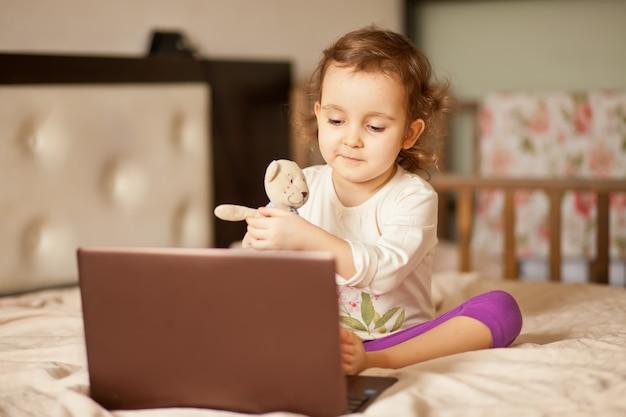 Mała śliczna dziewczyna siedzi na łóżku i używa cyfrowego pastylka laptopu notatnika. zadzwoń do znajomych lub rodziców online.