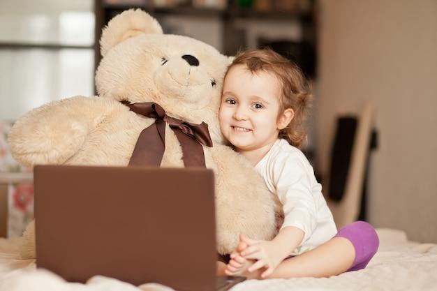Mała śliczna dziewczyna siedzi na łóżku z dużym misiem i używa cyfrowego laptopu notatnika pastylkę. zadzwoń do znajomych lub rodziców online.
