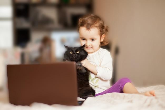 Mała śliczna dziewczyna siedzi na łóżku z ulubionym zwierzę domowe kotem i używa cyfrowego laptopu notatnika pastylkę. zadzwoń do znajomych lub rodziców online.