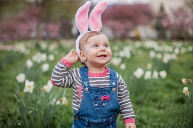 Mała śliczna dziewczyna stojąca na trawie w pobliżu żonkili