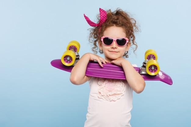 Mała śliczna dziewczyna trzyma deskorolkę
