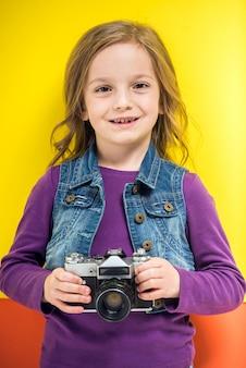 Mała śliczna dziewczyna trzyma retro fotografii kamerę
