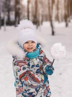 Mała śliczna dziewczyna trzyma śnieżkę zimą w parku
