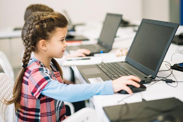 Mała śliczna dziewczyna używa laptop w sala lekcyjnej