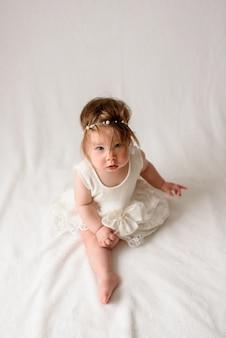 Mała śliczna dziewczyna w białej sukni i bandaż na głowie siedzi na białej powierzchni