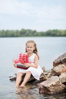 Mała śliczna dziewczyna w białej sukni i czerwonych żaglach. dziecko siedzi na skale nad morzem z zabawkowym statkiem.