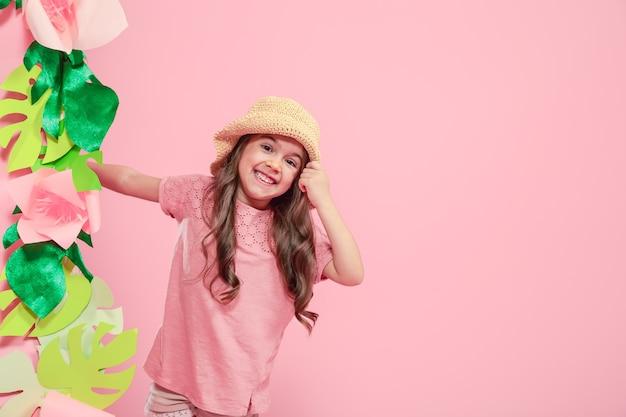 Mała śliczna dziewczyna w letnim kapeluszu na kolor na białym tle różowe tło z papierowymi kwiatami, miejsce na tekst, koncepcja reklamy letniej, strzelanie do studia
