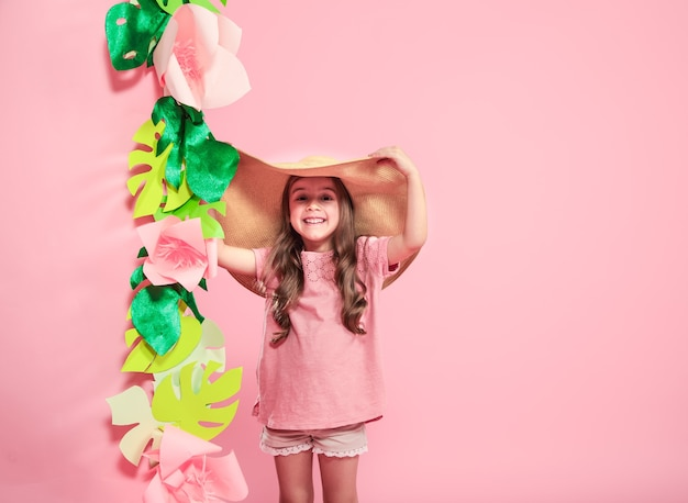 Mała śliczna dziewczyna w letnim kapeluszu na kolorowym tle