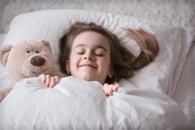 Mała śliczna dziewczyna w łóżku z zabawką