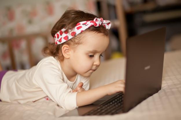 Mała śliczna dziewczyna w medycznej masce kłama na łóżku i używa cyfrowego pastylki laptopu notatnika. zadzwoń do znajomych lub rodziców online.