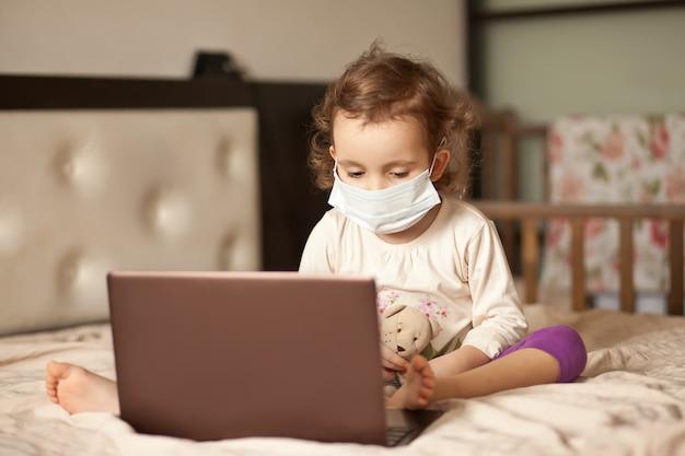Mała śliczna dziewczyna w medycznej masce siedzi na łóżku i używa cyfrowego pastylki laptopu notatnika. zadzwoń do znajomych lub rodziców online.