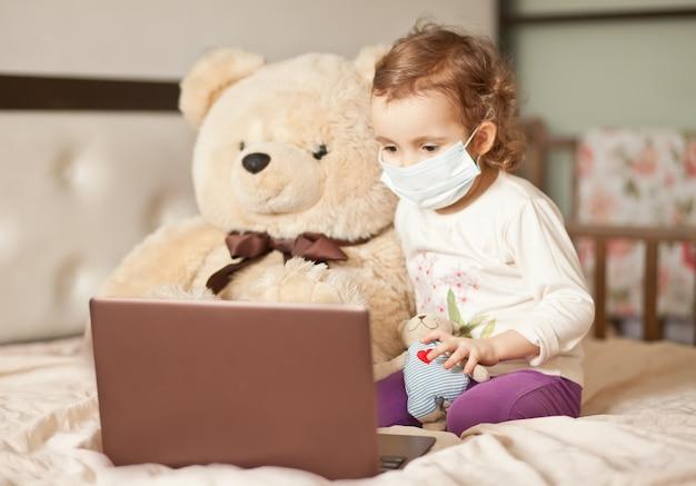 Mała śliczna dziewczyna w medycznej masce siedzi na łóżku z dużym misiem i używa cyfrowego notatnika laptopu pastylkę. zadzwoń do znajomych lub rodziców online.