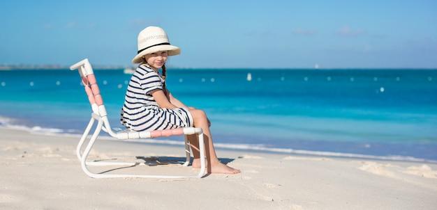 Mała śliczna dziewczyna w plażowym krześle relaksuje na karaibskim wakacje