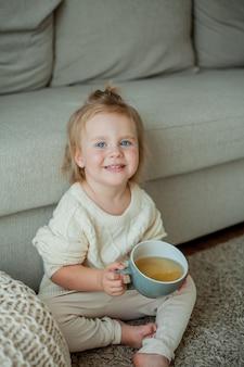 Mała śliczna dziewczyna w pomarańczowym swetrze pije herbatę. przytulny portret dziewczyny siedzącej w domu. spadek.