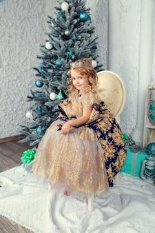 Mała śliczna dziewczyna w princess sukni blisko nowego roku drzewa, piękny bożenarodzeniowy wystrój