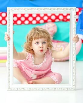Mała śliczna dziewczyna w różowym kostiumu obsiadaniu na podłoga i ono uśmiecha się nad drewnianą biel ramą.