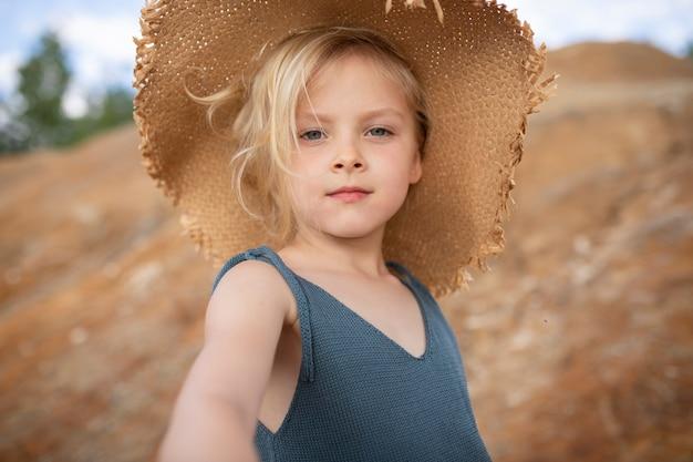 Mała śliczna dziewczyna w stylowe ubrania na tle skał